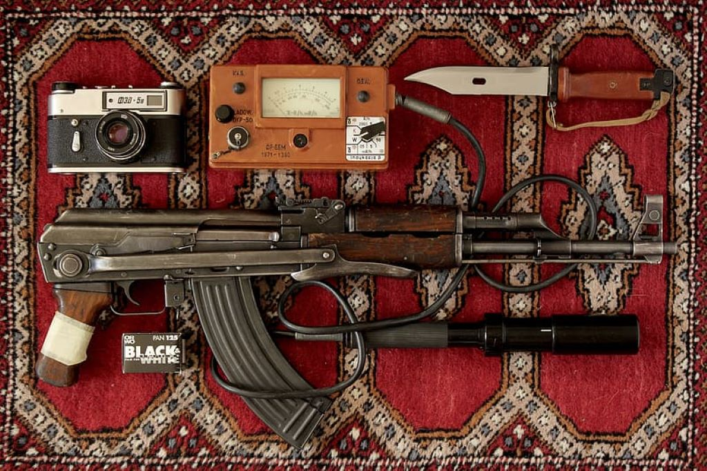 black and brown ak-47 near black and gray camera and tactical knife place on red and gray area rug