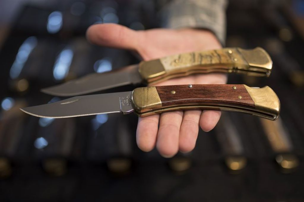 man holds two folding knives on palm