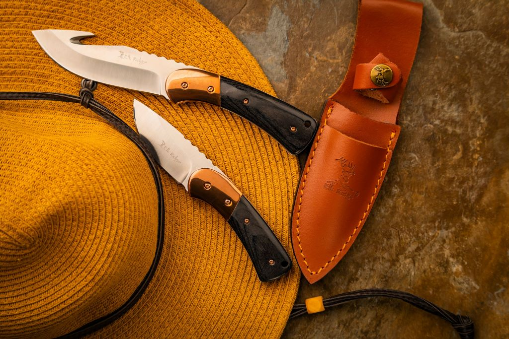 two edc fixed blades on top of a hat