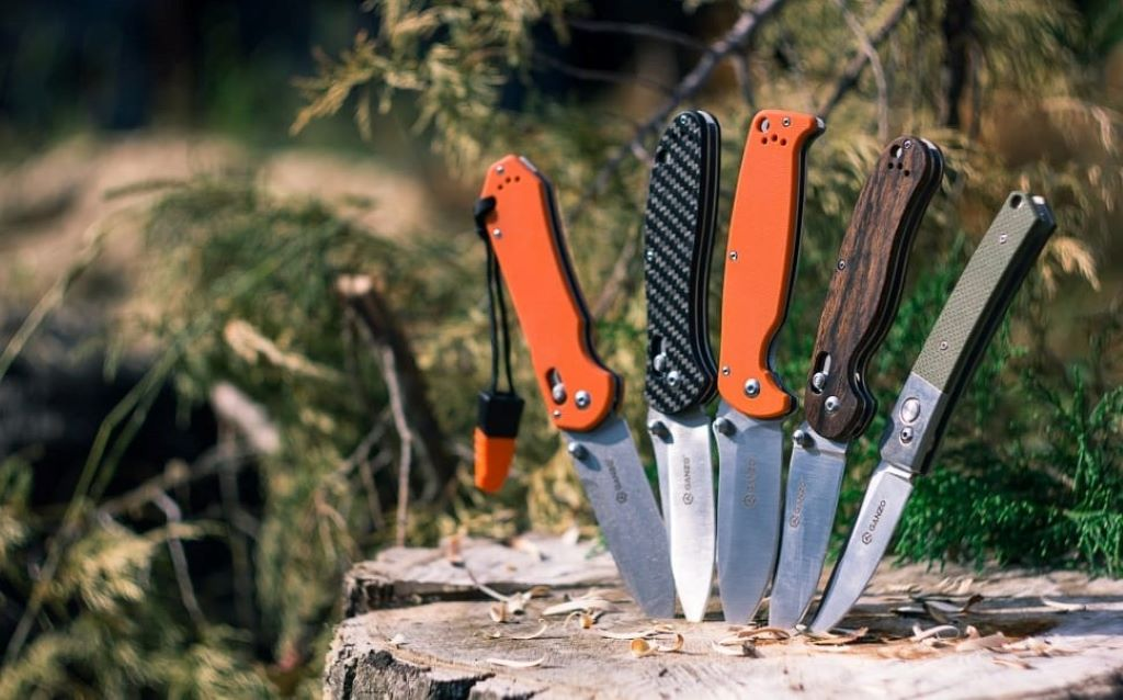5 switch knives stabbed on brown wooden tree trunk